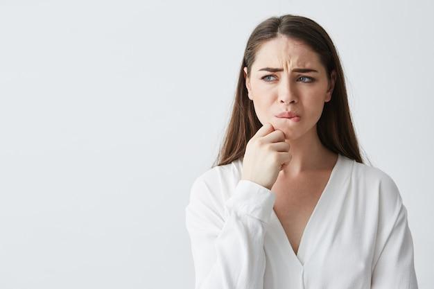 Ritratto di giovane ragazza nervosa del brunette che pensa guardando in mano laterale della tenuta sul mento.