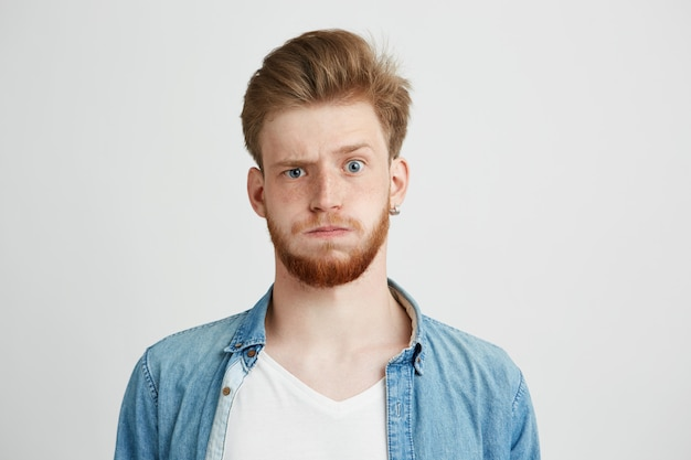 Portrait of nervous young man with beard raising up brow.