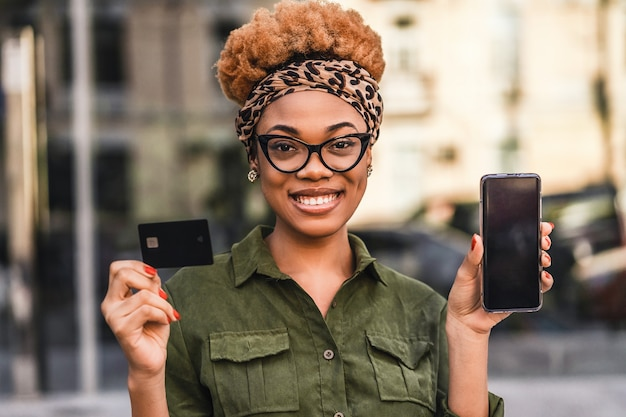 Portrait of nice afro american woman in glasses holding credit card and using cellphone while standing outdoors