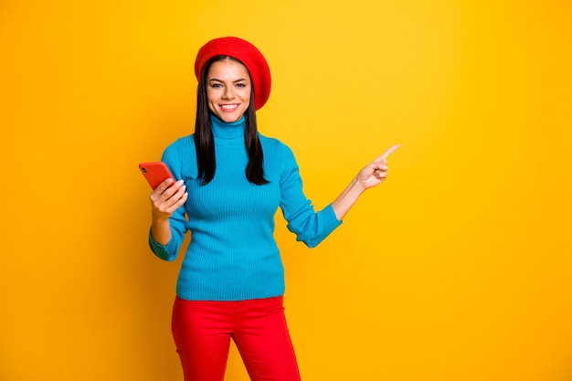 Portrait of nice attractive cheerful cheery girl using cell showing copy space ad easy fast shopping order buying online purchase isolated over bright vivid shine vibrant yellow color wall