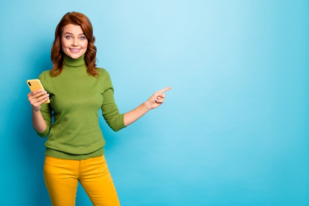 Portrait of nice attractive cheerful glad wavy-haired girl using cell showing copy space online shopping service isolated on bright vivid shine vibrant blue turquoise teal color wall