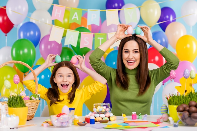 Portrait of nice attractive creative glad cheerful cheery girls holding in hands over head eggs like rabbit ears having fun bright vivid shine vibrant blue color