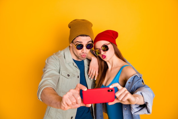 Portrait of   nice attractive funny cheerful childish couple friends friendship taking selfie sending air kiss travel isolated over bright vivid shine vibrant yellow color background