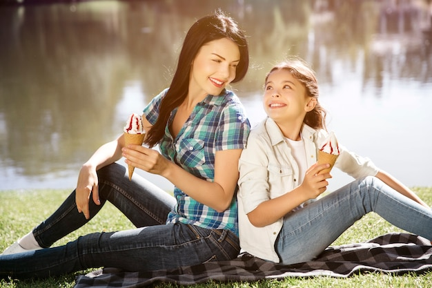 A portrait of nice and attractive girls sitting together back to back and looking at each other. they are holding two cons of ice cream and smiling.