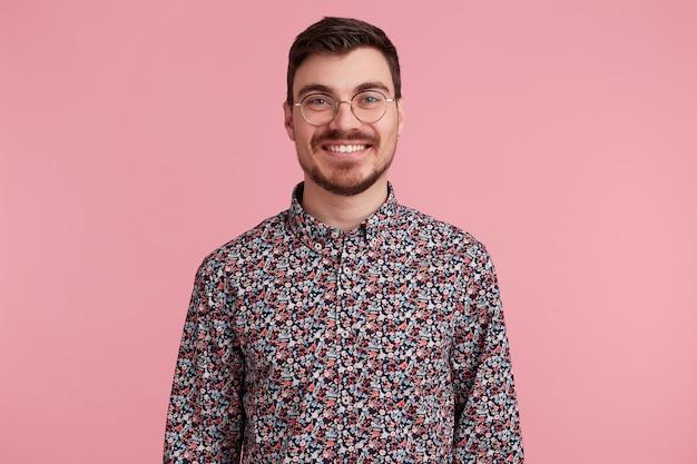 Ritratto di un bel giovane attraente bello con gli occhiali con i capelli scuri non rasati con barba e baffi in maglietta colorata piacevolmente sorridente, isolato