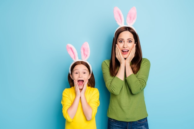 Portrait of nice attractive lovely charming pretty amazed cheerful cheery girls wearing rabbit ears having fun isolated over bright vivid shine vibrant blue color