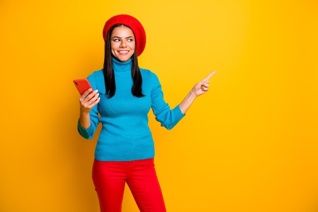 Portrait of nice attractive lovely cheerful cheery girl using cell showing copy space ad advert store boutique shopping online isolated over bright vivid shine vibrant yellow color wall