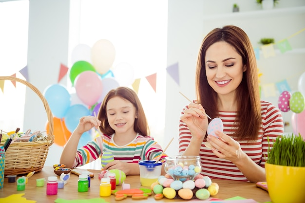 Portrait of nice attractive lovely cheerful cheery girls small little daughter creating festal decor preparing april day spending time in white light interior room house indoors
