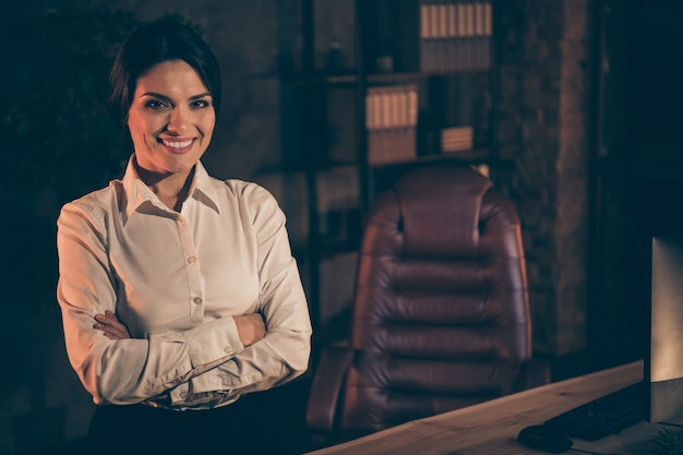 Portrait of nice attractive lovely chic classy stylish cheerful cheery content lady financier economist attorney lawyer agent broker company owner folded arms at night dark work place station