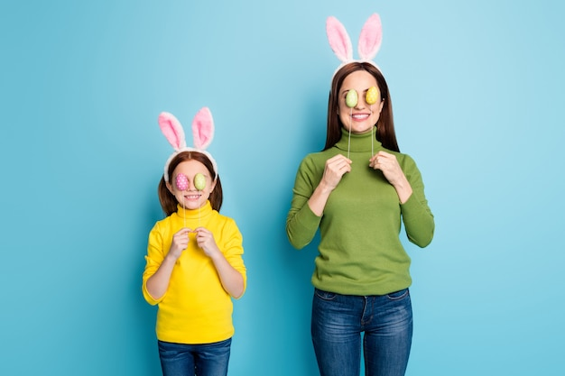 Portrait of nice attractive lovely childish playful cheerful cheery girls covering eyes with eggs sticks having fun isolated over bright vivid shine vibrant blue color