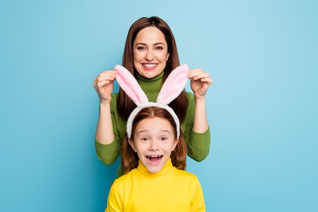 Portrait of nice attractive lovely funny charming pretty cheerful cheery girls mom touching daughter's rabbit ears having fun isolated over bright vivid shine vibrant blue color