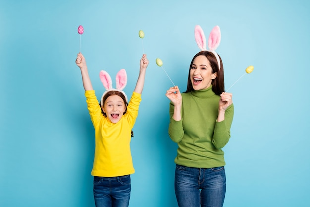 Portrait of nice attractive lovely glad cheerful cheery girls mom mum holding in hands eggs sticks having fun isolated over bright vivid shine vibrant blue color