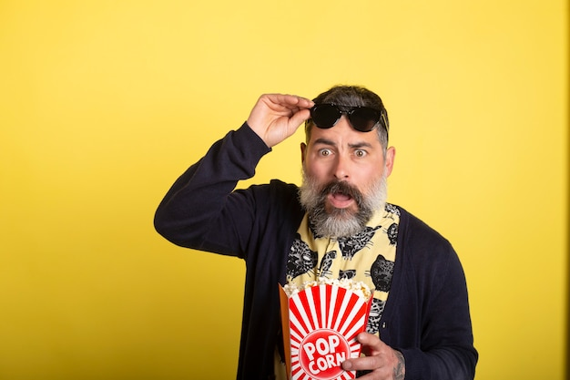 Portrait of nice attractive scared bearded man lifting sunglasses with yellow shirt and blue jacket eating popcorn watching scary video isolated on yellow background.
