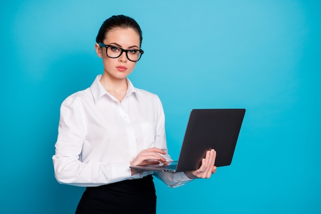 Portrait of nice attractive skilled serious smart lady holding in hands laptop isolated over vibrant blue color background