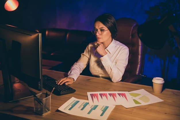 Portrait of nice attractive stylish chic concentrated lady top executive manager company agency owner preparing report plan strategy investment ratio result at night dark work place station