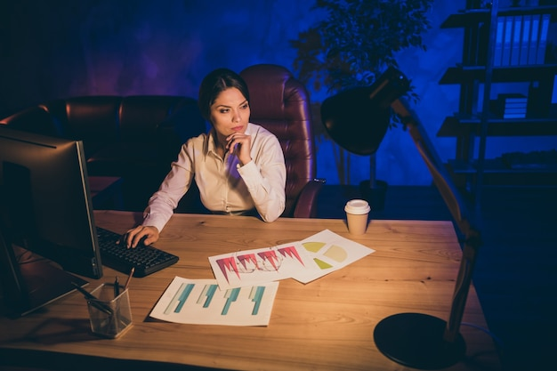 Portrait of nice attractive stylish chic focused lady top executive manager finance company agency owner creating new startup strategy investment ratio deposit p at night dark work place station