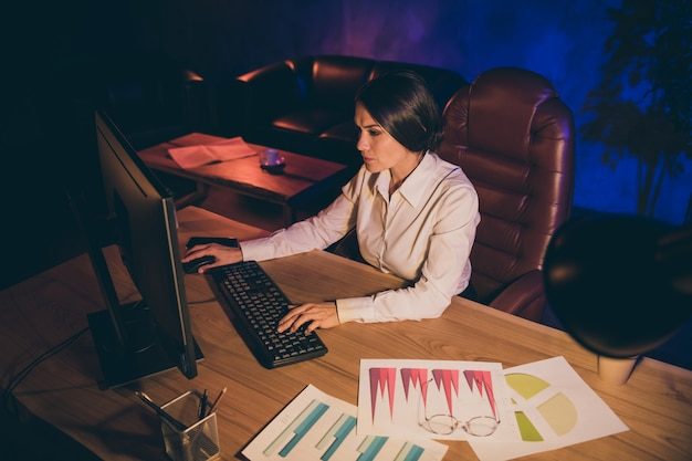 Portrait of nice attractive stylish lady top executive manager preparing report strategy investment ratio result interest invest analyzing economy audit account at night dark work place station