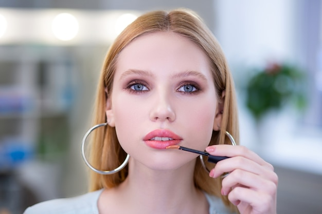 Portrait of a nice attractive woman looking in front of her while applying a pink lipstick
