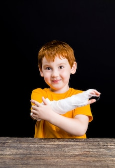 Portrait of a nice boy with red hair with minor injuries bandaging himself with a medical bandage, a boy with medical equipment during self treatment and first aid, closeup