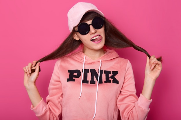 Portrait of nice cute attractive woman pulling her hair asides, wears shortened hoodie, cap and stylish black sunglasses, shows her tounge