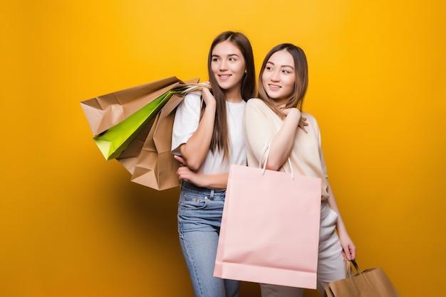 Ritratto di belle ragazze carine che abbracciano tenendo nelle mani che trasportano nuovo acquisto cool isolato sulla parete gialla