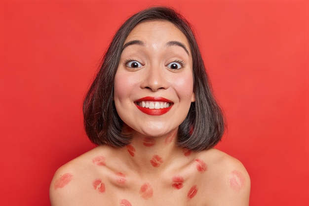 Portrait of nice lovely asian woman smiles broadly shows white teeth has smooth skin lips traces on naked body very happy after romantic date with boyfriend stands against vivid red wall.