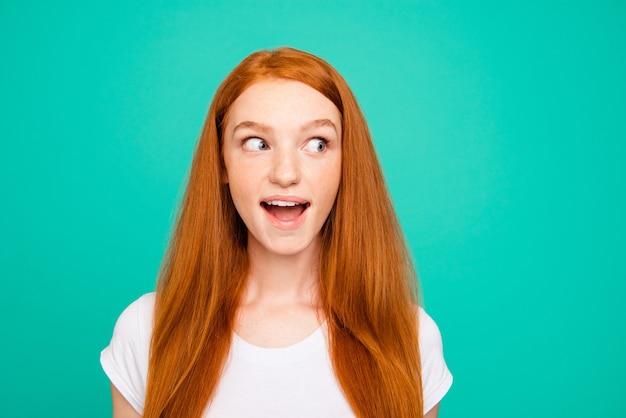 ターコイズブルーの壁に隔離された肖像画の素敵な赤毛の女の子