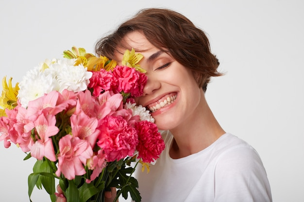Portrait of nice short haired girl in white blank t-shirt, holding a bouquet, covers face with flowers, standing over white background with closed eyes.