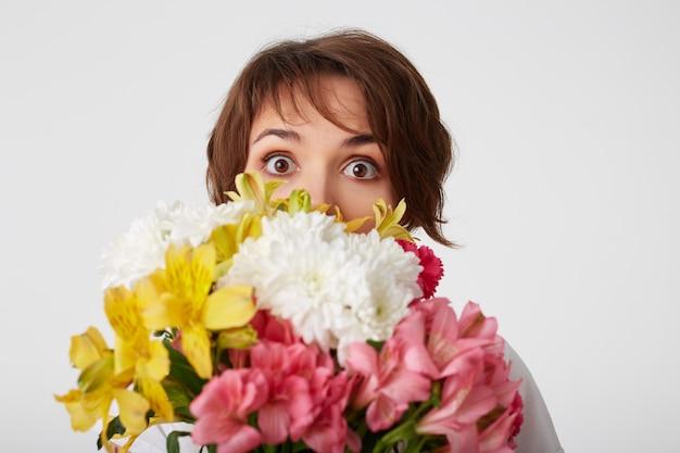 Ritratto di una bella ragazza dai capelli corti in maglietta bianca vuota, che tiene un mazzo, che fa capolino da dietro i fiori, in piedi su sfondo bianco con gli occhi spalancati.