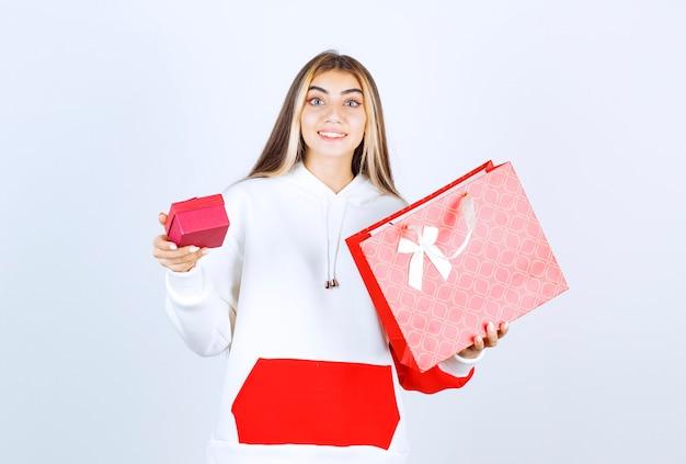 Ritratto di una bella donna modella in piedi e tiene in mano una borsa con una piccola scatola