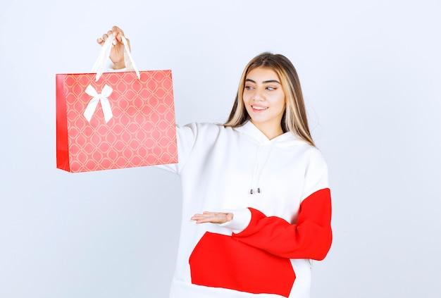 Ritratto di una bella modella in piedi che mostra una borsa regalo