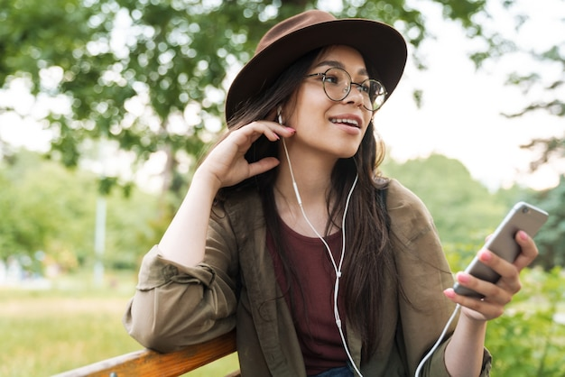 Portrait of nice woman with long dark hair wearing hat and eyeglasses using earphones and smartphone in green park