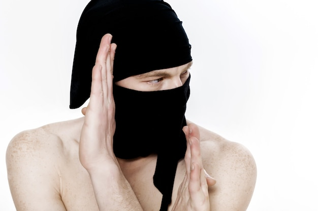 Portrait of ninja man in a black mask on white background