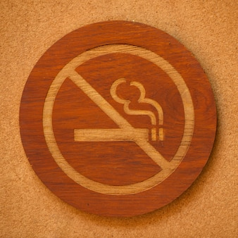 Portrait of no smoking wooden sign against brown wall