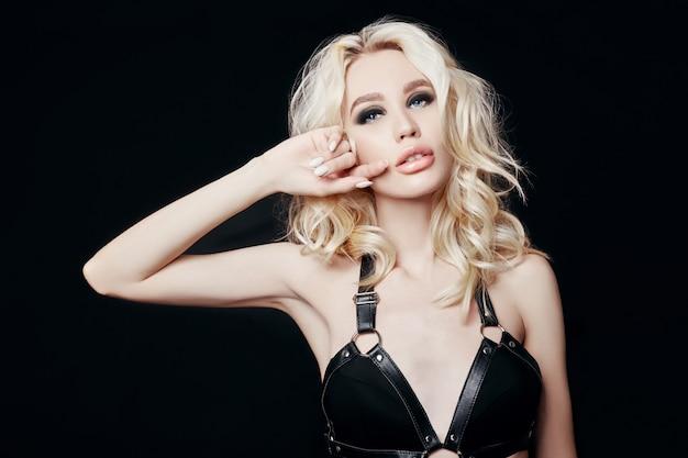 Портрет обнаженной сексуальной блондинки в черном нижнем белье с идеальным телом и элегантной прической на черном