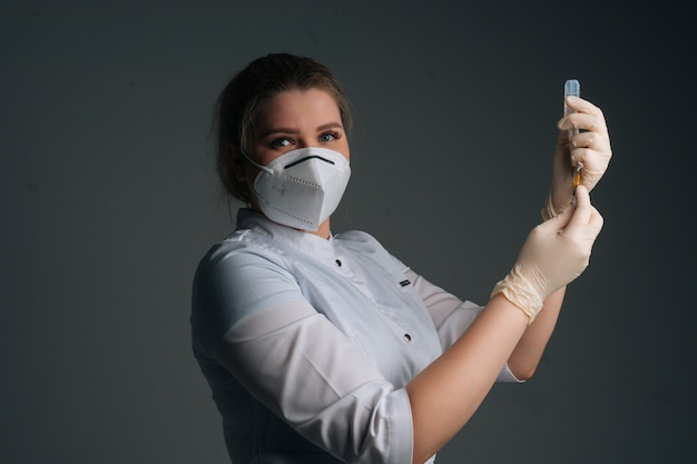 Portrait of nurse in blue gloves and face mask holding and filling up vaccine to syringe on black isolated background, looking at camera. doctor preparing to give injection of coronavirus vaccine.