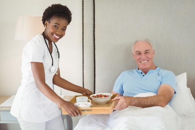 Portrait of nurse serving breakfast to senior patient