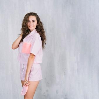 Ritratto o sorridente giovane donna in piedi davanti al muro
