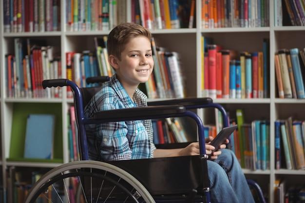 Портрет школьника-инвалида, держащего цифровой планшет в библиотеке