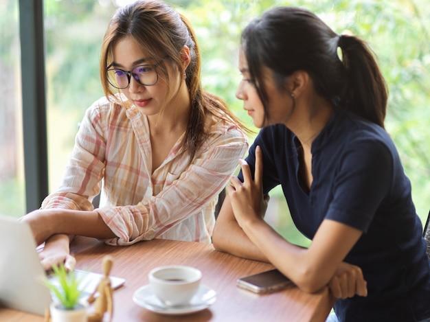 Портрет 2 деловых женщин, обсуждающих и смотрящих на ноутбук