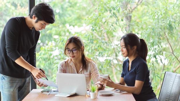 Портрет 3 рабочих, встречающихся и обсуждающих в конференц-зале с ноутбуком и финансовыми бумагами