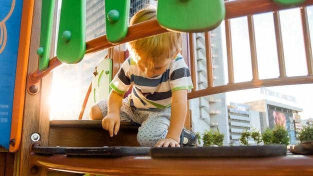 Портрет 3-летнего маленького мальчика, идущего и ползущего по высокому деревянному мосту на детской площадке в парке. дети играют и веселятся на детской площадке