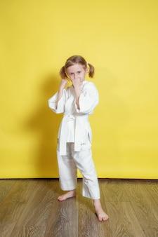 기모노 5 살 백인 여자의 초상화 집에서 노란색 배경에 대해 가라테 연습