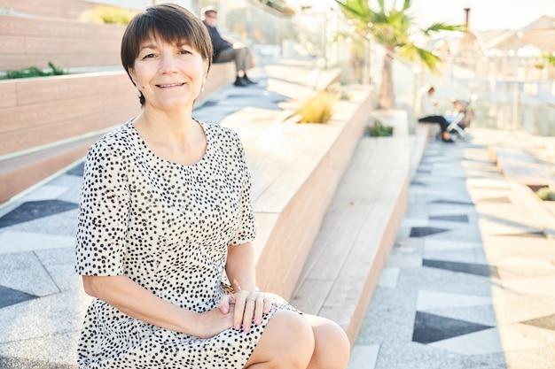 ベンチの公園に座って笑っている50歳の幸せな白人女性、大人の健康な本物の女性の肖像画