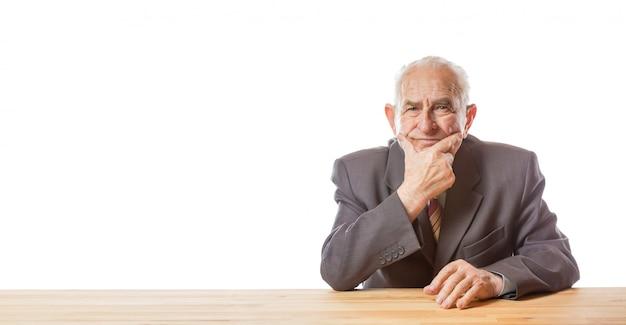Портрет 90-ти летнего старшего красивого человека в костюме сидя на таблице, думая и держа его руку на подбородке против изолированной белой предпосылки.