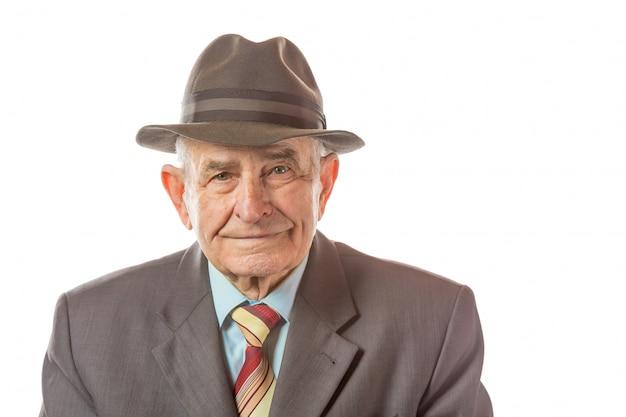 Портрет 90-ти летнего старшего человека в ретро шлеме смотря камеру изолированную на белой предпосылке.