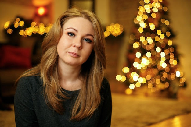 クリスマスツリーとお祝いのクリスマスインテリアで30歳の美しい赤毛の女性の肖像画