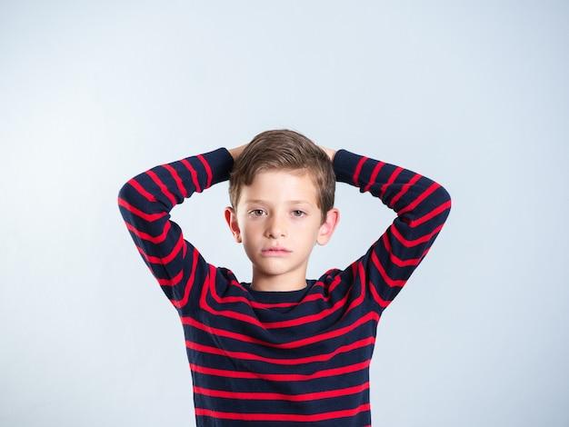 Портрет 7-летнего мальчика, выглядящего очень серьезно, изолированного на сером фоне