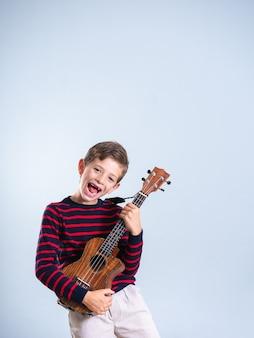 灰色の背景に分離されたウクレレを演奏する7歳の少年の肖像画