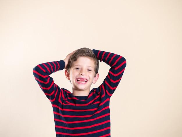 前歯が欠けている、孤立している、コピースペースで笑っている7歳の少年の肖像画